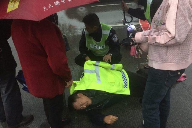 老人雨中跌倒,交警脱去警用雨衣为其撑伞等救援